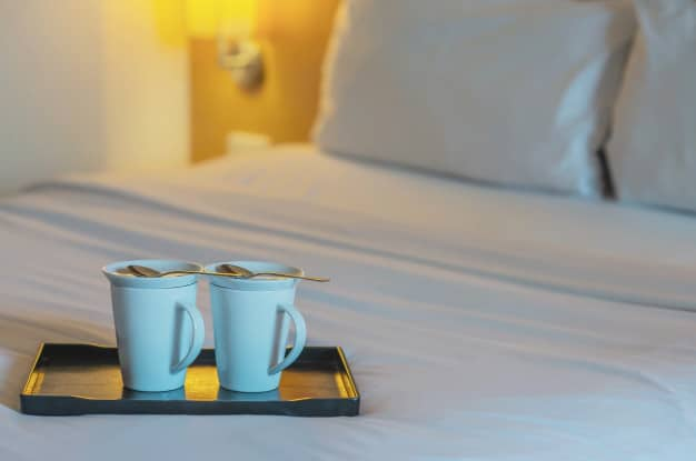 close-up-twin-welcome-coffee-cup-white-bed-hotel-room-hotel-well-hospitality-vacation-travel-concept_1150-13594